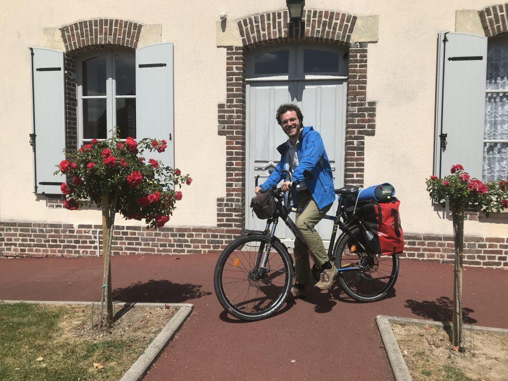 Ulysse Blau devant la mairie de Fumichon. Comme son étude était auto-gérée et auto-financée, il a réalisé son voyage à vélo pour minimiser les coûts. / Crédits : Ulysse Blau
